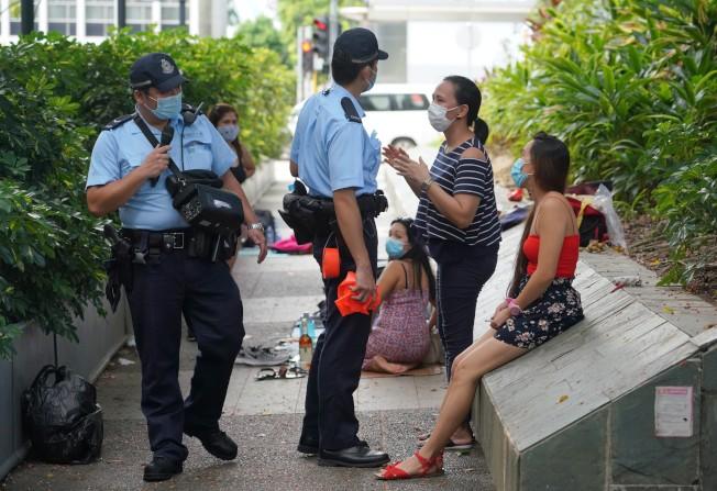 香港警方和勞工處等政府部門9日在中環等外傭聚集場所進行聯合巡查行動,勸喻外傭和市民遵守「限聚令」和「口罩令」。(中通社)