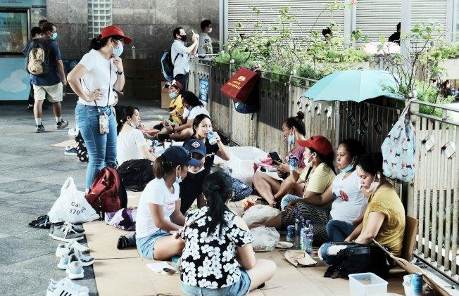 疫情嚴峻之下,9日繼續有大批外傭於香港中環一帶聚集,不少外傭群組均超過兩人,更有部分外傭除下口罩聊天及進食。(中新社)