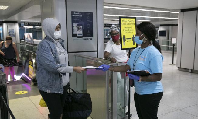 為防病例輸入,紐約州市採取強厲措施,在機場、鐵路站公路站,都設置檢查站,對自外州來的旅客採取實名登記追蹤。圖為在曼哈頓巴士總站,工作人員(右)正在進行登記。(美聯社)