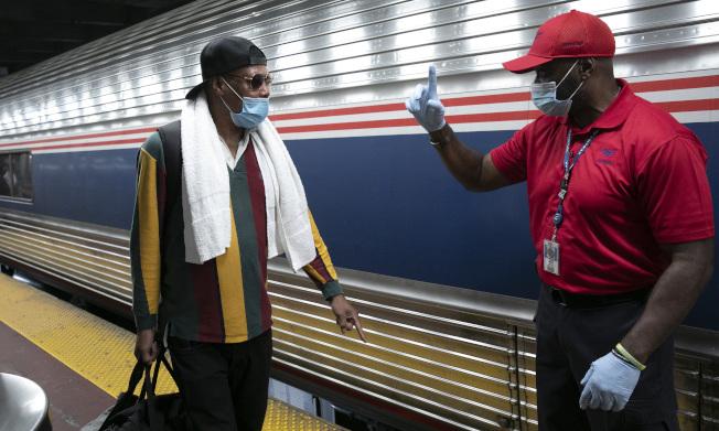 為防病例輸入,紐約州市採取強厲措施,在機場、鐵路站公路站,都設置檢查站,對自外州來的旅客採取實名登記追蹤。圖為在曼哈頓大中央火車總站,工作人員(右)正在進行登記。(美聯社)