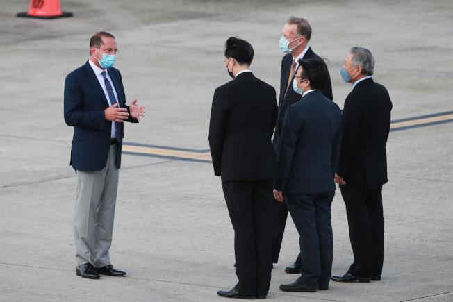 美國衛生部長阿查爾(左)9日下午率團搭乘專機抵達台灣,他是1979年以來訪台層級最高、也是6年來首位訪台的美國內閣官員,在松山機場上外交部次長田中光(背對右起)、疾管署署長周志浩與AIT處長酈英傑(右二)一同接機,而阿查爾下機後拱手不握手,向前來接機大夥致意。(記者許正宏/攝影)