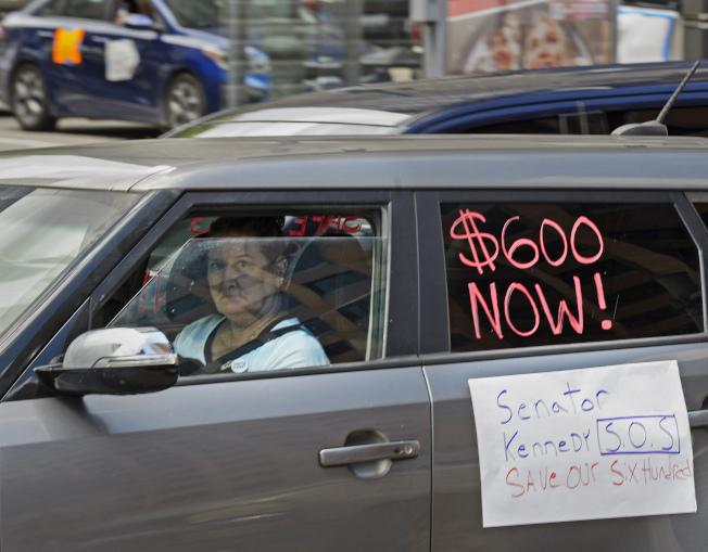 川普總統簽發行政命可暫時延長失業津貼,但從原本的600元降到400元,其中各州自行吸收100元。圖為在路易西安納州紐奧良市失業者上月22日駕車到聯邦大樓前示威,打出「馬上發600元」的標語。(美聯社)