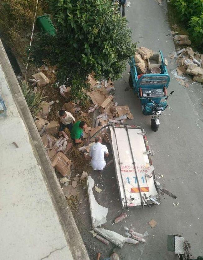 事故現場附近居民瘋搶車上豬肉。(取材自微博)