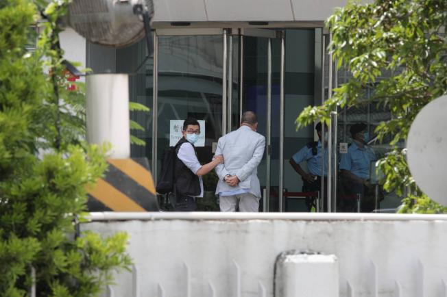 香港蘋果日報創辦人黎智英被扣上手銬,押送到蘋果日報大樓內協助查證。(中央社/讀者提供)