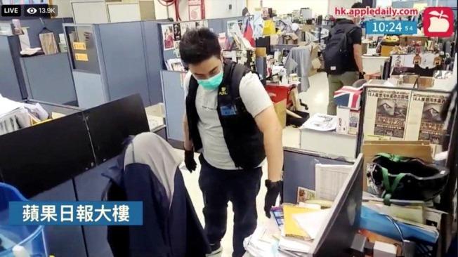 在香港蘋果的同步直播中,可見有港警翻查辦公桌上的資料文件。 (路透/香港蘋果日報直播截圖)