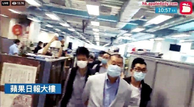 香港媒體大亨黎智英,10日上午無預警遭港警以涉嫌詐欺與觸犯《港區國安法》為由逮捕。近中午時分,他被帶往正被搜查中的壹傳媒大樓。 (路透/香港蘋果日報直播截圖)