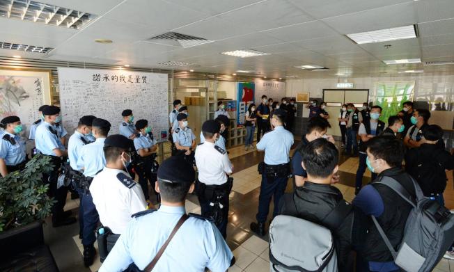 大批警員在蘋果日報大樓內進行搜查。(中央社)