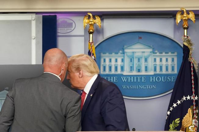 川普總統靠近特勤人員,被告知要立刻離開現場。(路透)