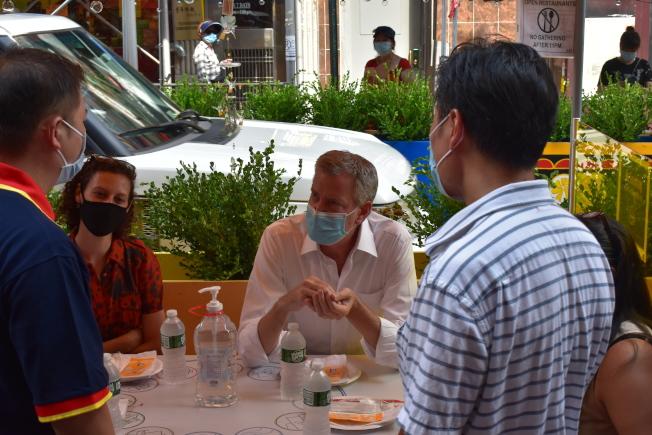 白思豪坐在華埠街頭享受戶外用餐。(記者顏嘉瑩/攝影)