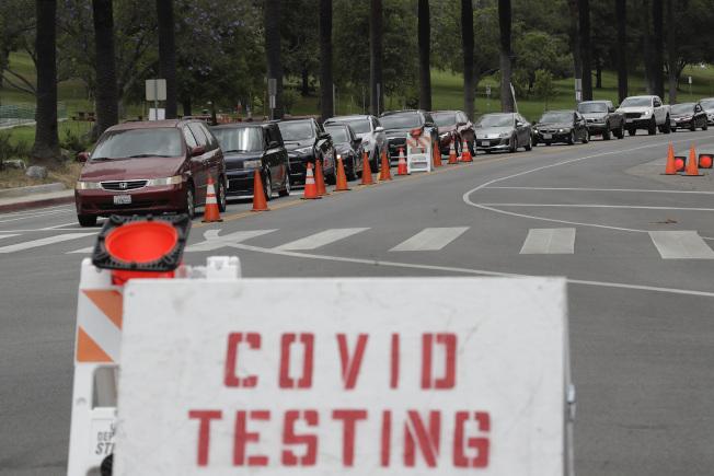 美國新冠確診數字仍在攀升。加州官方7月底承認檢測數字出問題,大約有 30 萬例未被列入紀錄。圖為洛杉磯道奇體育館6月設立「得來速」新冠病毒測試站點,是全市最新、規模最大的測試站點。(美聯社)