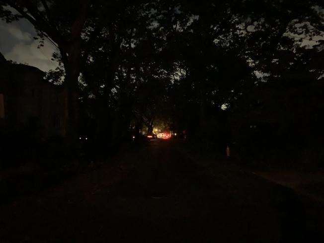 熱帶風暴過後,斷電的社區裡一片漆黑,遠處的光亮是維修車輛,但修復的時間卻遙遙無期。(記者曹健╱攝影)
