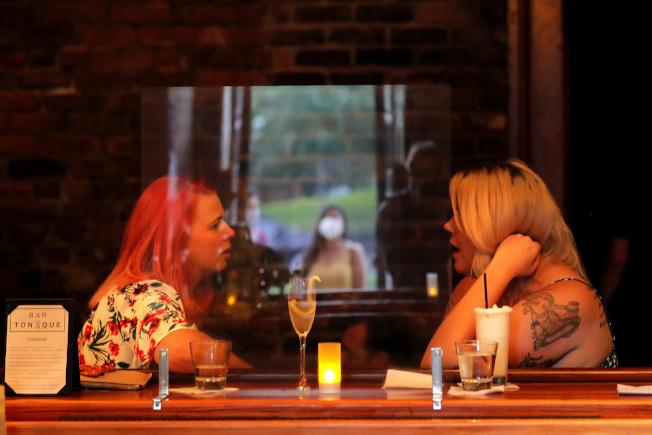 路易斯安納州紐奧良市(New Orleans)一家酒吧內,兩名顧客在聊天。(美聯社)