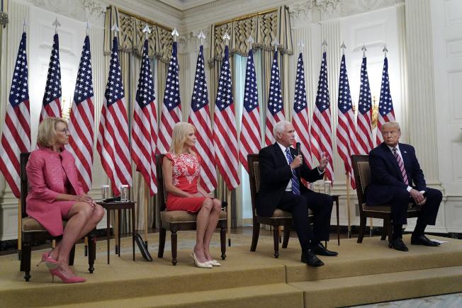 副總統潘斯(右二)與民主黨準副總統候選人賀錦麗的政見辯論將是火花四濺,針鋒相對。圖為川普總統(右)與潘斯12日在白宮與教育部長蓓西‧狄弗斯(左),舉行學校遠距教學的討論會。(美聯社)