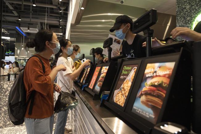 中美關係惡化,網路傳出有中國民眾抵制美國貨。美國人氣漢堡Shake Shack昨天在北京的首家門市開業,大批北京民眾排隊嘗鮮。(美聯社)