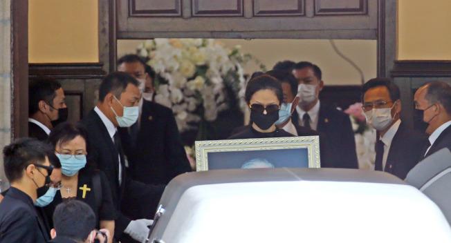 李登輝孫女李坤儀拿著李前總統的照片走出教會。(記者杜建重/攝影)
