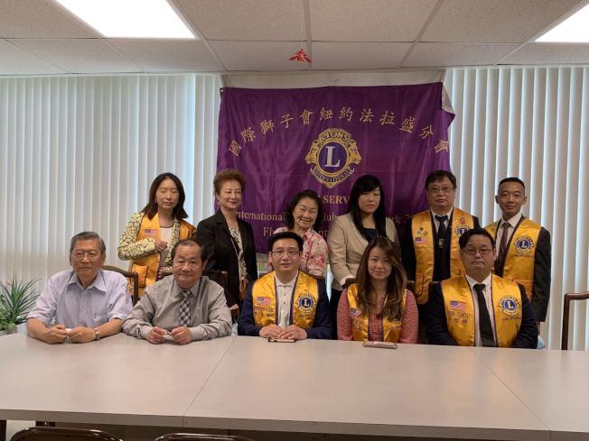 廖本卿(前排左三起)向吳凱茜交接國際獅子會法拉盛分會會長一職。(國際獅子會法拉盛分會提供)