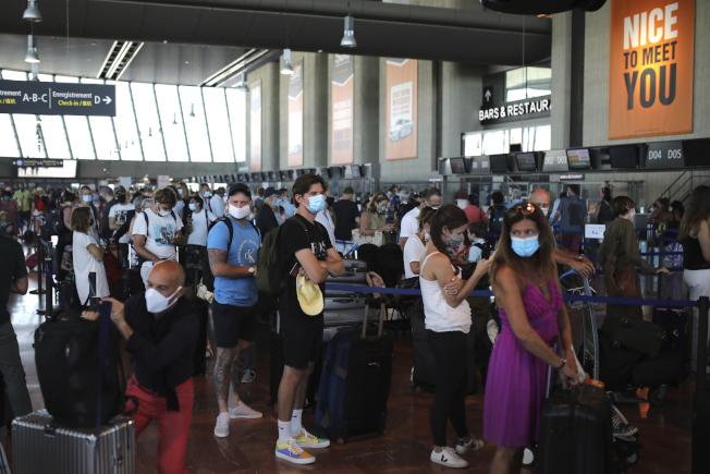英國政府決定對法國實施檢疫限制,在法國度假的英國人考慮回國,圖為民眾14日在法國南部尼斯機場辦理搭乘英國航空飛往倫敦希斯洛機場的航班。(美聯社)
