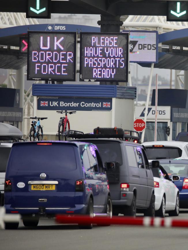 英國政府決定對法國實施檢疫限制,在法國度假的英國人考慮回國,圖為民眾14日在法國加萊排隊辦理搭乘跨海渡輪手續。 (美聯社)