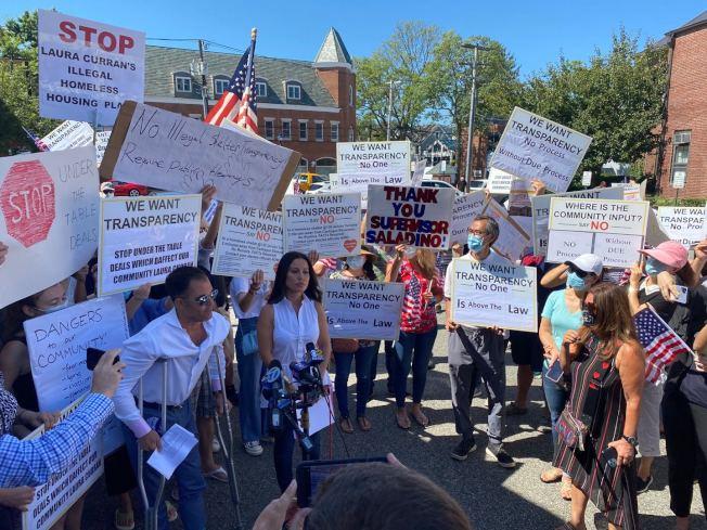 18日上午数百名居民在蚝湾镇政府前集会,感谢镇政府倾听民意,「忧心的杰瑞柯父母」团体,向镇长提交一份2000馀名居民的连署签名,反对游民所计画。(朱崴提供)