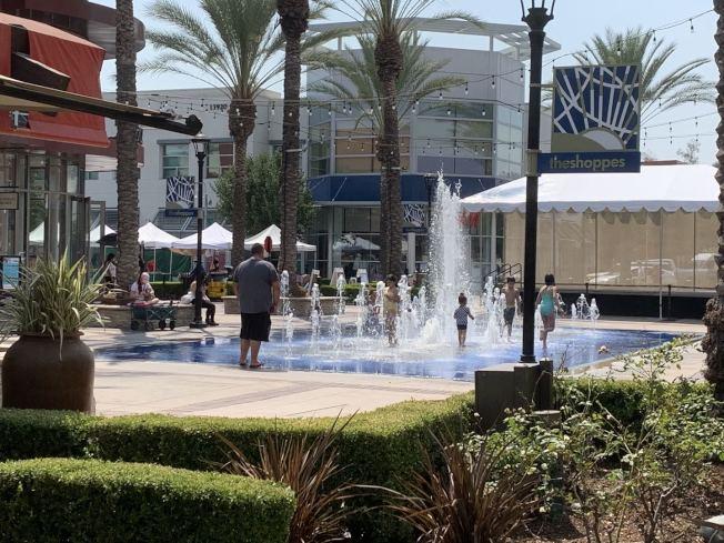 家長陪孩子避暑,到奇諾岡步行街戲水。(記者啟鉻/攝影)