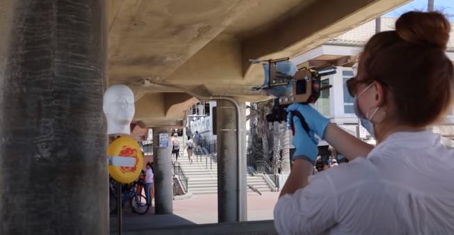 路人試著對假人發射口罩。(影片截圖)