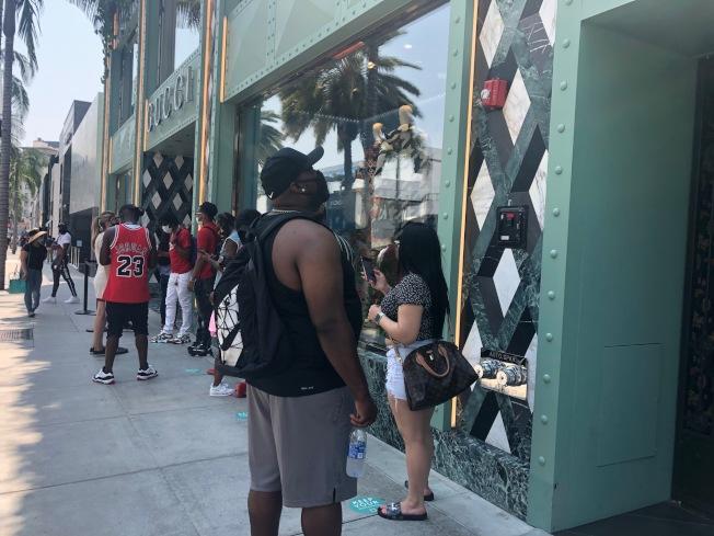 在名牌店門口排隊的人們。(記者張宏/攝影)