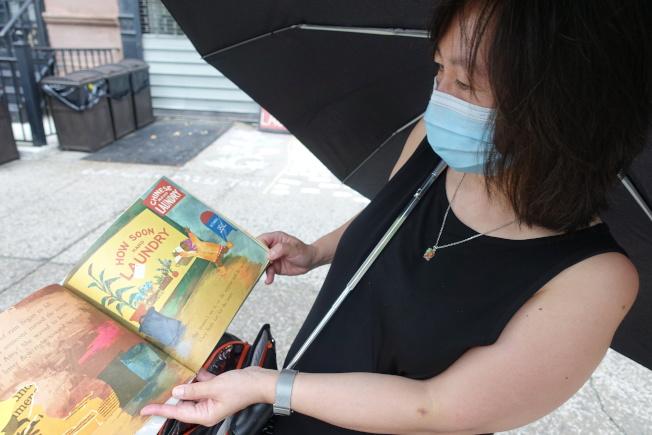 祖父也曾經營洗衣店的陳雪媚曾買過一本來自1960年代的兒童書,裡面就繪有華人開設洗衣店的圖案。(記者金春香/攝影)