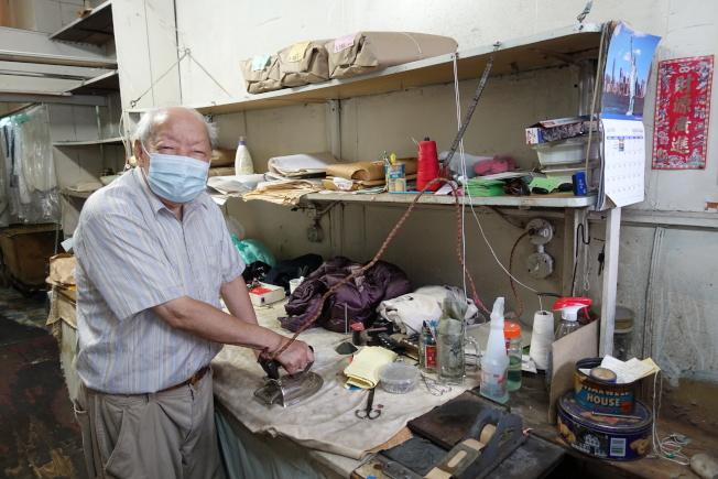 李洪森展示使用傳統熨斗熨燙衣物。(記者金春香/攝影)