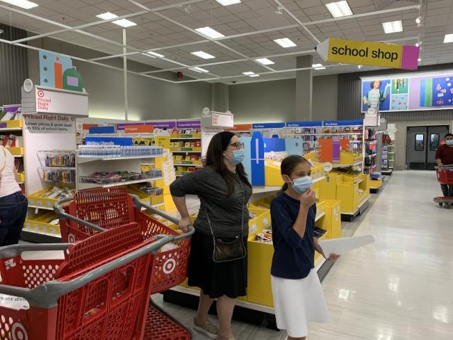 新學年將至,家長和學生戴口罩採購返校用品。(本報記者/攝影)