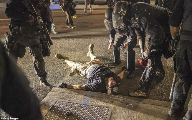 右派反示威人士29日遭到射殺後倒在街上,同行者在試圖急救。(Getty Images)