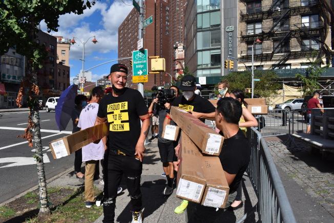 余雷蒙等人30日向華埠小商家購買食物,並在且林士果免費派送,吸引大批民眾排隊。(記者顏嘉瑩/攝影)