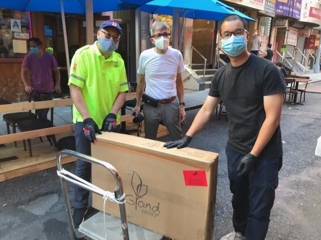 余雷蒙捐贈十組戶外用餐桌椅和陽傘給華埠商改區。(陳倩雯辦公室提供)