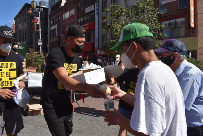余雷蒙(左二)將麵包派給華埠居民。(記者顏嘉瑩/攝影)