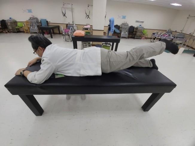 (圖2)簡易背部肌力訓練:俯臥姿勢,將一側下肢抬起,維持5秒,每次10下,做完再換另一邊,早晚各一次,力量足夠的話,亦可同時將上半身抬起。(圖:鄭彥昌提供)