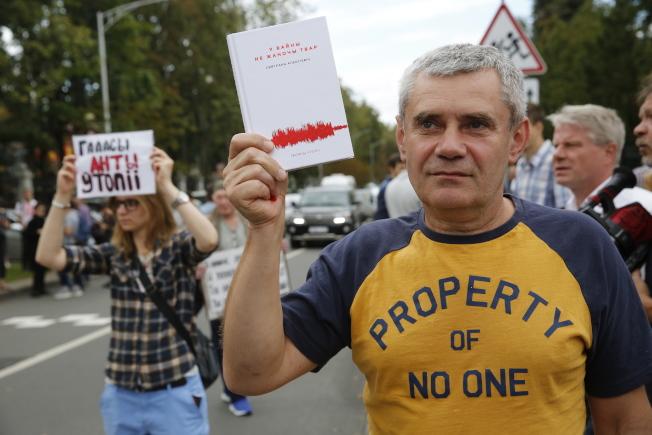 支持者拿著亞歷塞維奇的名著《戰爭沒有女人的臉》為她打氣。(歐新社)