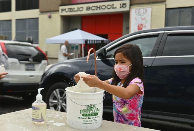 紐約市布魯克林一所公校門口,學生先洗手消毒再進入。(Getty Images)