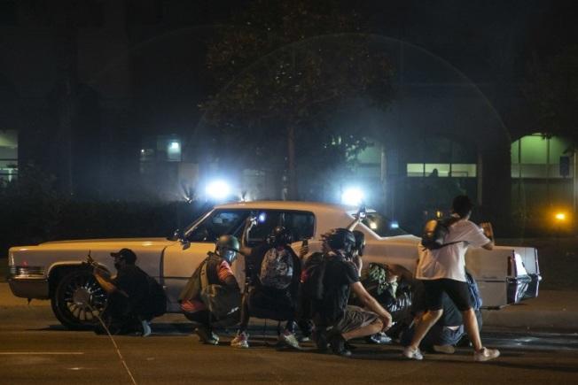 洛縣警局南洛杉磯分局外,警員發射催淚瓦斯,抗議民眾利用一輛車子作屏障。(洛杉磯時報)