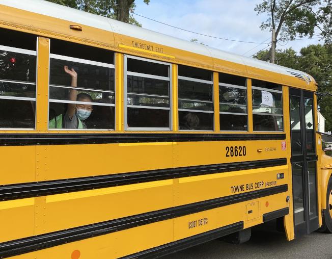 長島華裔小學生鍾Charlie,8日早上登上校車後與父母揮手告別。(文思提供)