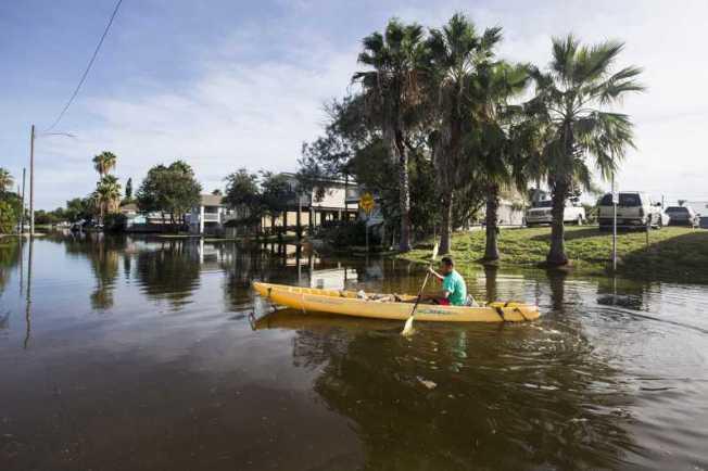 圖為早先蘿拉颶風過後,德州蓋文斯頓城的居民划獨木舟穿越街道。(美聯社)