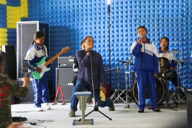 痛仰樂隊與海嘎小學的樂隊同台表演。(取材自北京青年報)